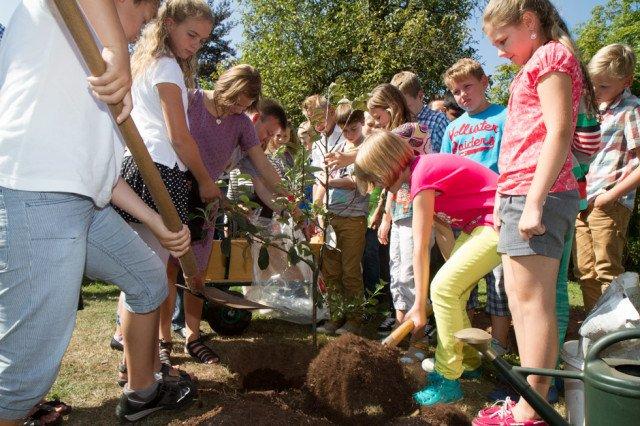 Zum Abschluss pflanzen die Schülerinnen und Schüler den Apfelbaum, der viele Früchte tragen soll. Foto: SMMP/Beer